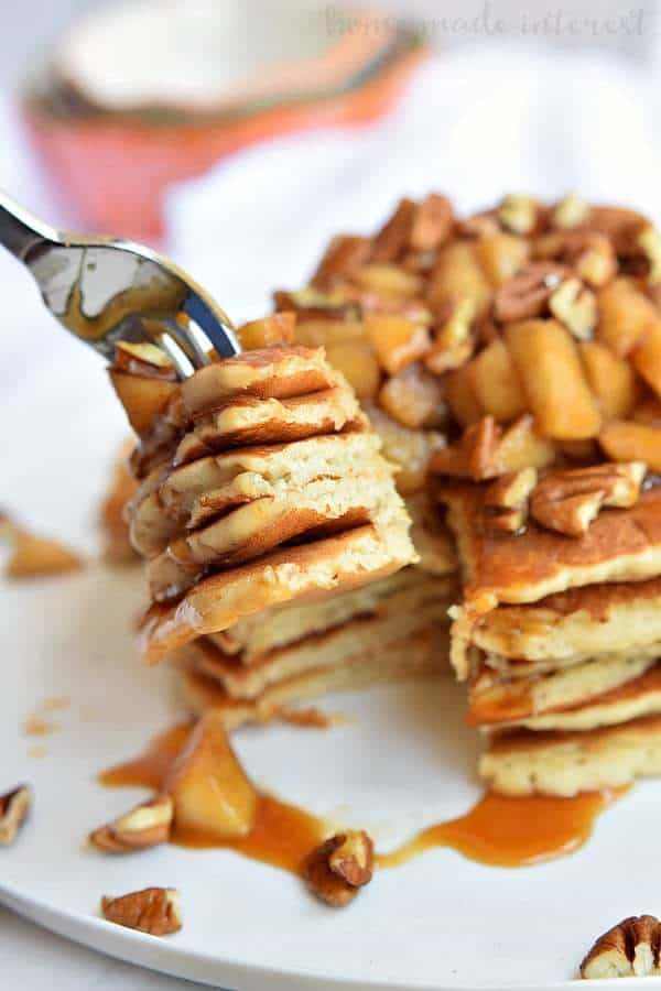 These Caramel Apple Pecan Pancakes are a fall breakfast recipe made with light and fluffy pancakes topped with caramel sauce, baked apples, and pecans.