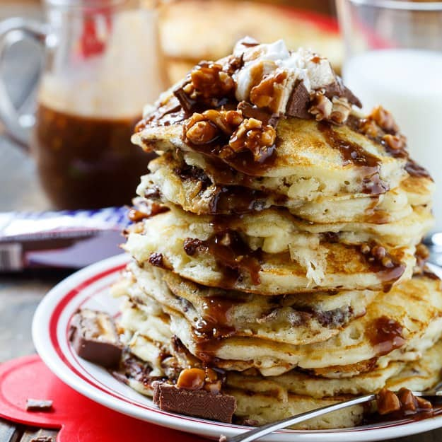 Snickers Pancakes with Snickers Syrup make a truly special breakfast. Chopped candy bars are added to the batter and melted to make a syrup