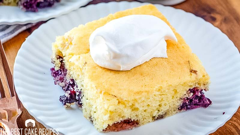 A piece of cake on a paper plate, with Cherries and whipped cream