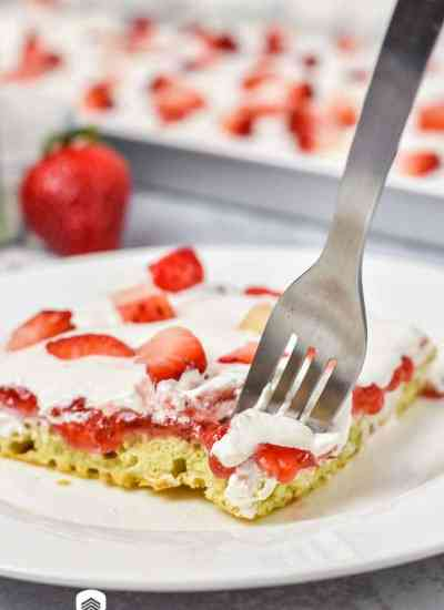 A close up of a piece of cake on a plate, with Strawberries