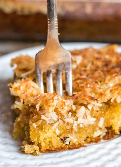 coffee cake with coconut topping on a plate with a fork