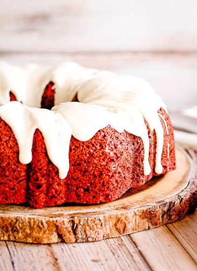 red velvet bundt cake with cream cheese glaze on a wooden plate