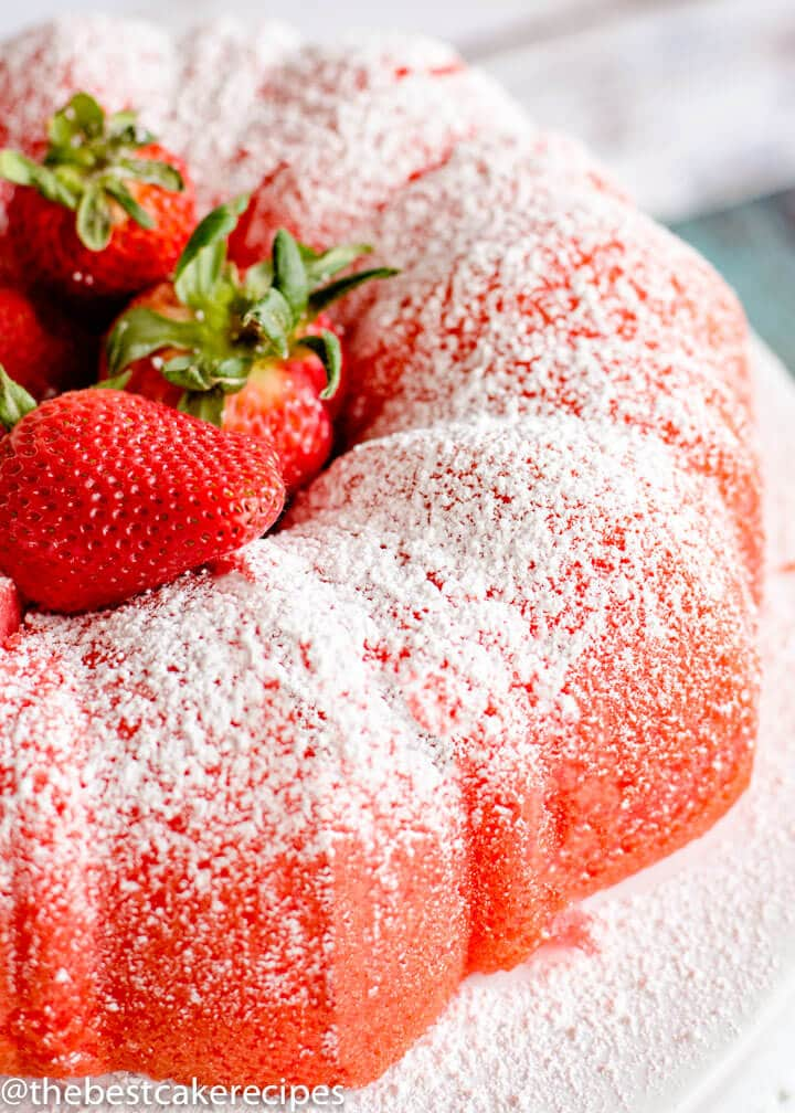 Filled Strawberry Bundt Cake with fresh strawberries on a plate