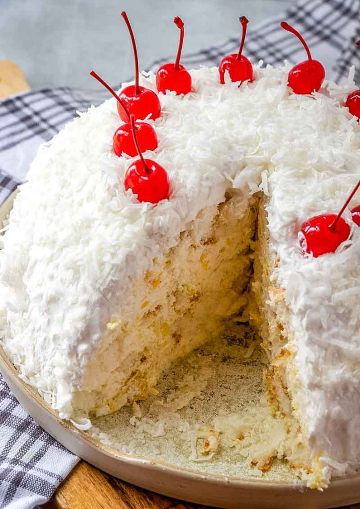 angel food snowball cake with cherries on top, one slice missing