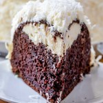 A piece of chocolate cake on a plate, with Cream cheese and coconut frosting