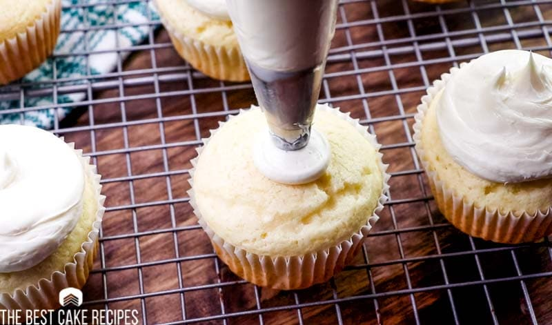 piping frosting on a cupcake