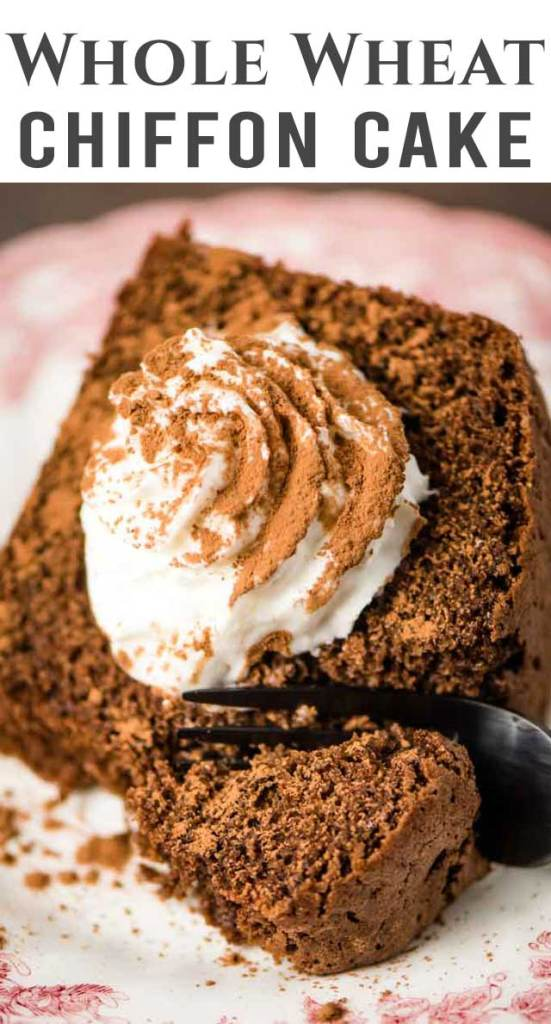 A piece of chocolate cake on a plate, with whipped cream and cocoa powder