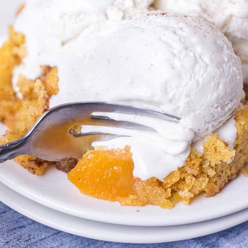 Peach Dump Cake with ice cream on a plate