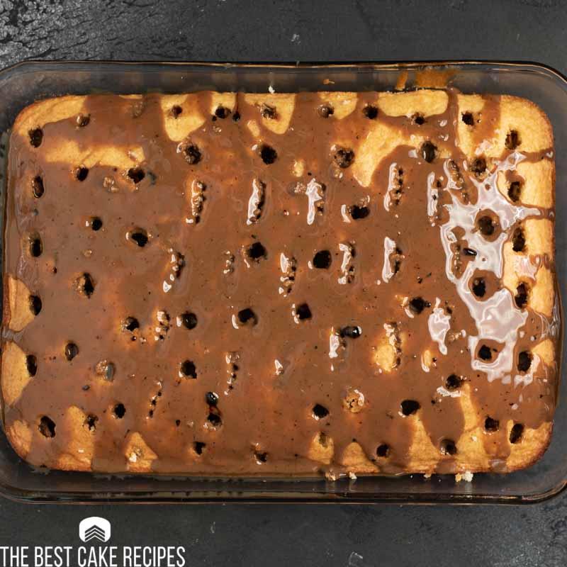 white cake with poke holes and coffee glaze