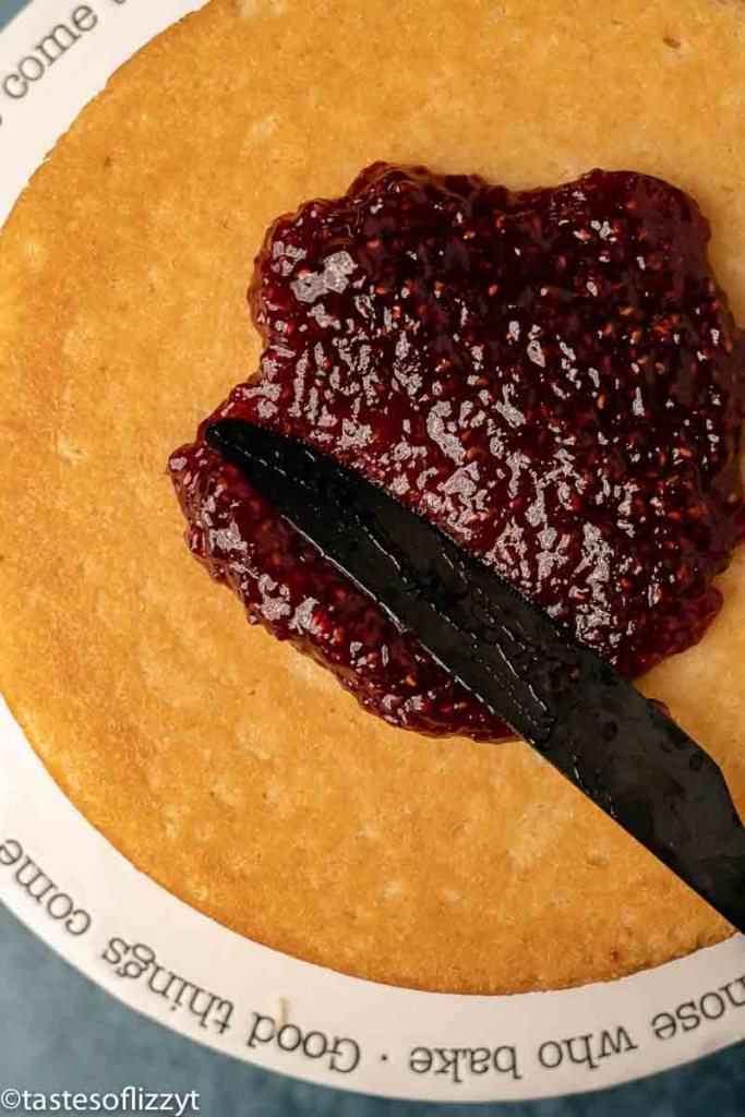 spreading raspberry jam on white cake