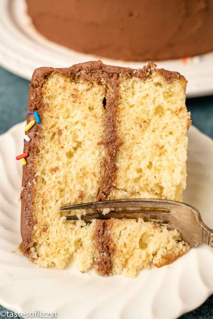 slice of yellow cake on a plate with a fork