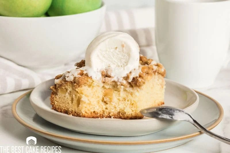 apple crisp coffee cake on a plate with a bite out of it