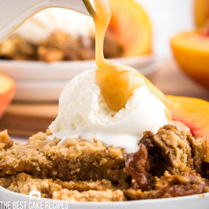 pouring caramel over peach dump cake