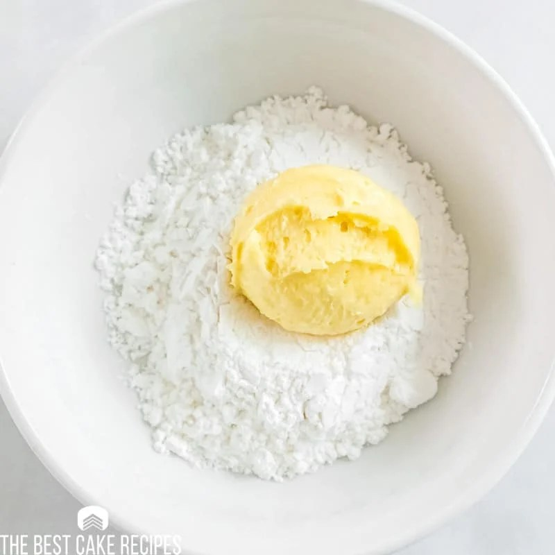 lemon cookie dough in a bowl of powdered sugar