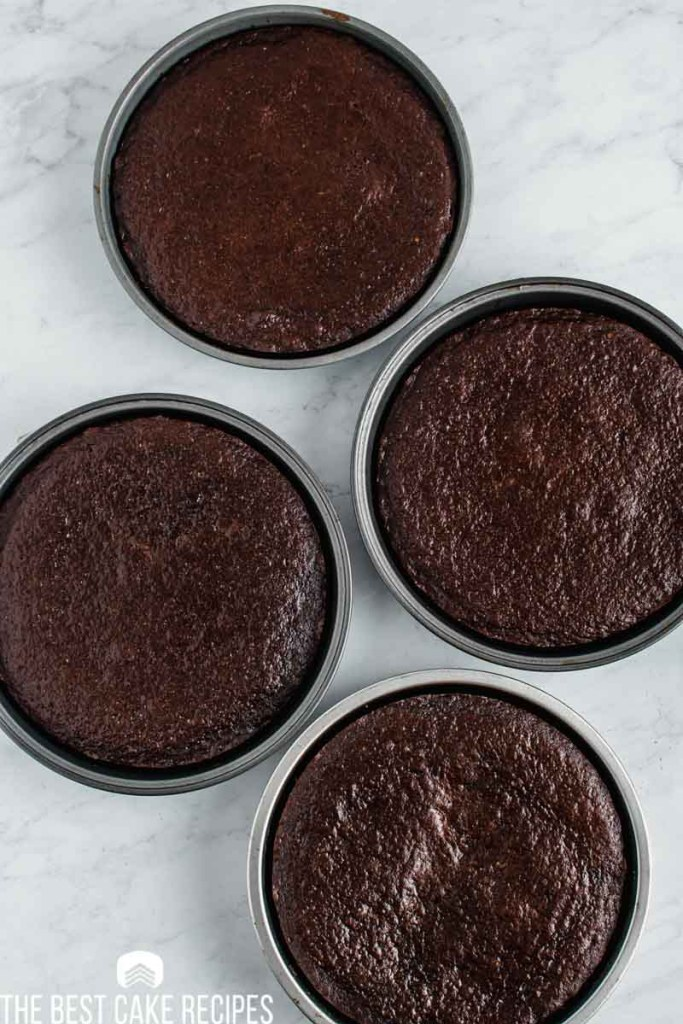 4 chocolate cake layers in baking pans