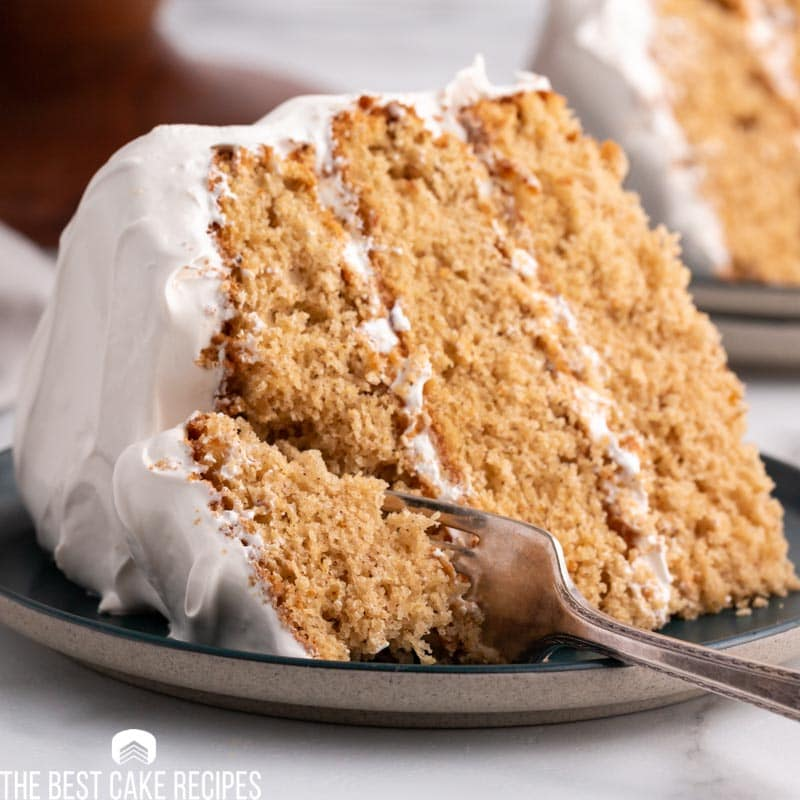 a slice of 3 layer spice cake on a plate with a fork