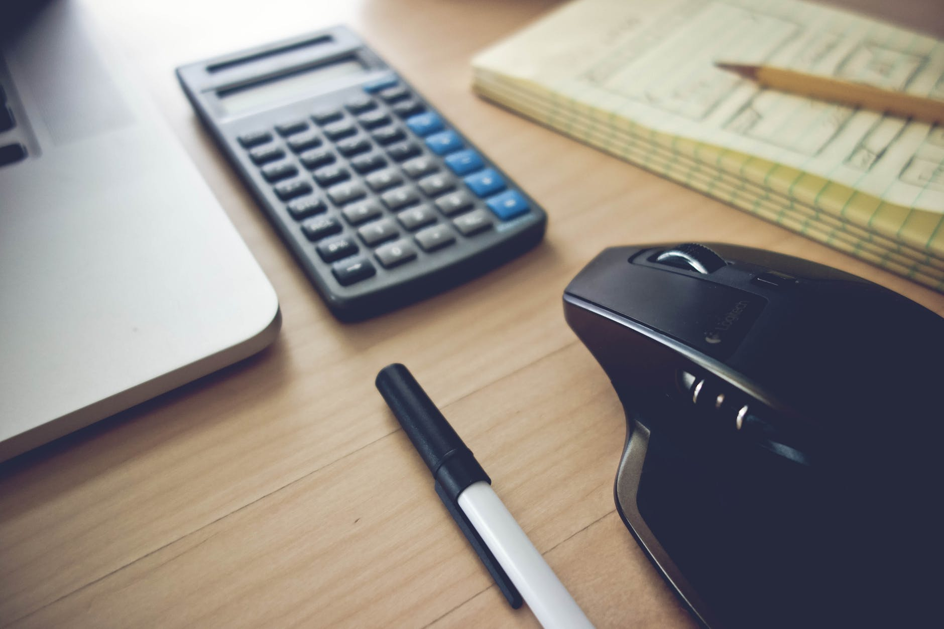 calculator, pen, mouse and a paper on the top