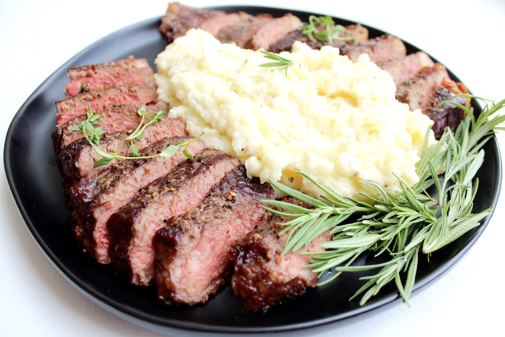 cooked steak with mashed potatoes and fresh rosemary