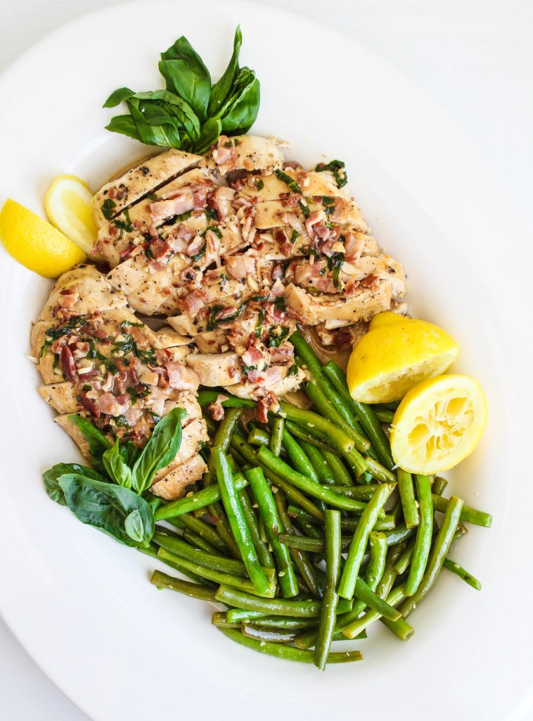 Sliced chicken breast on a large white platter with fresh green beans and lemon wedges and fresh basil on the side