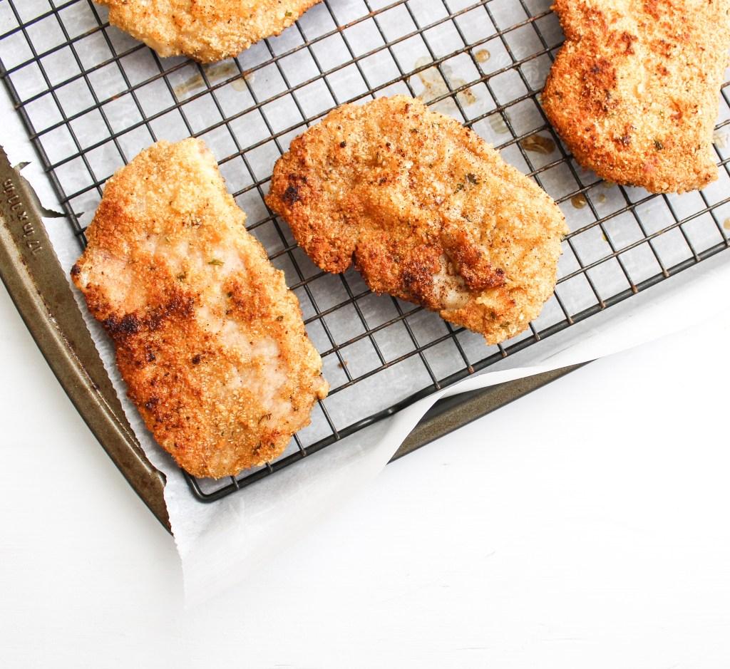 crispy breaded pork cutlets sitting on a baking rack