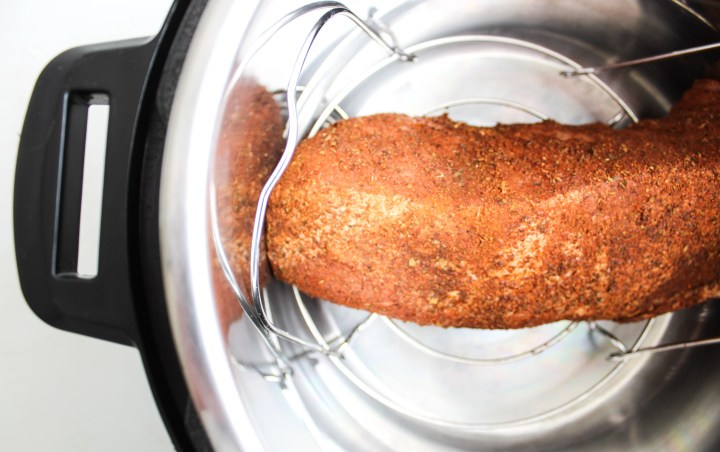 Pork tenderloin coated with spice sitting on the trivet in the Instant Pot