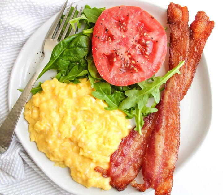 A plate filled with creamy scrambled eggs, crispy bacon, fresh greens and a slice of tomato