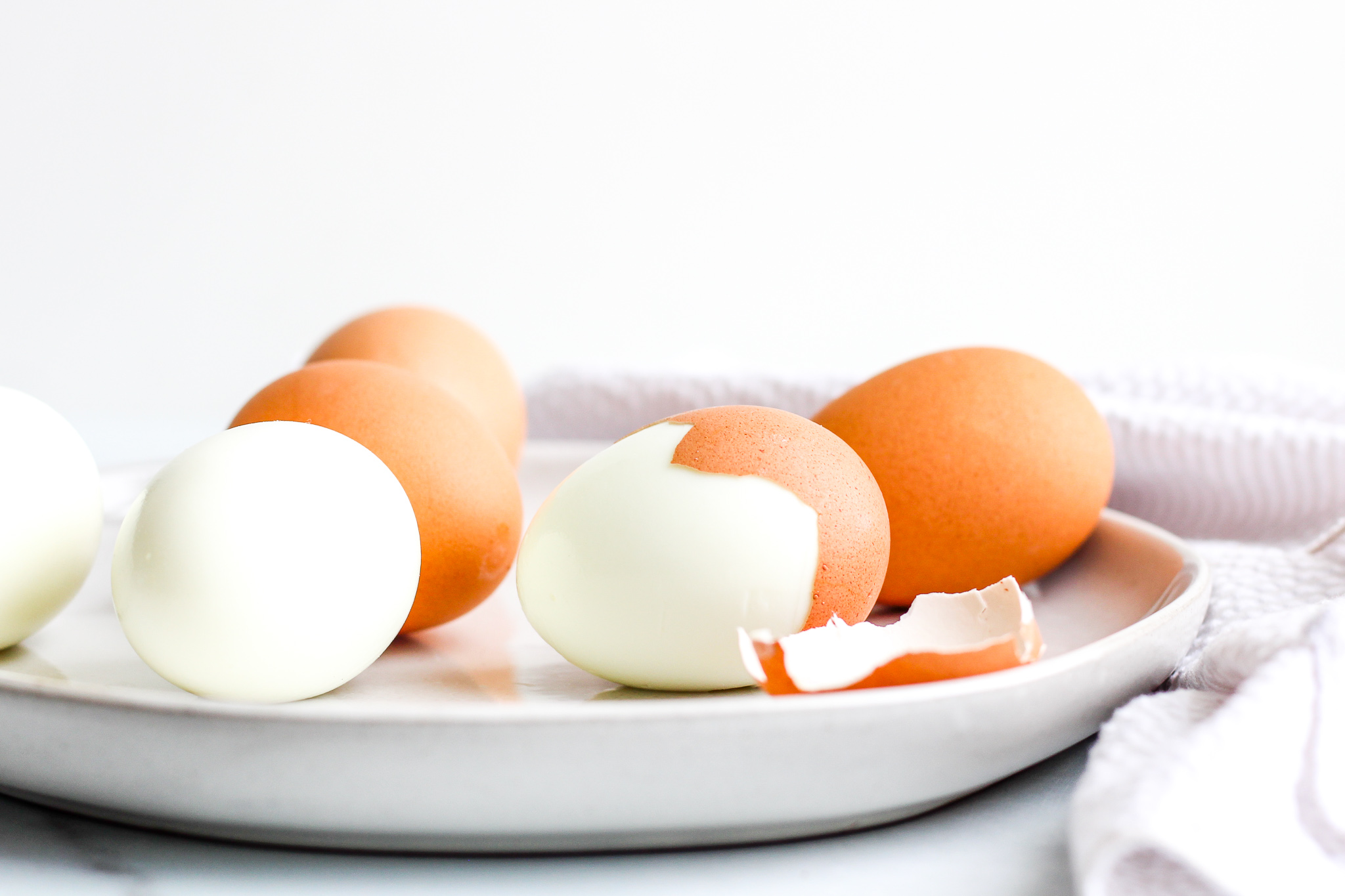 Hardboiled eggs on a white plate, one is peeled and some in their shells