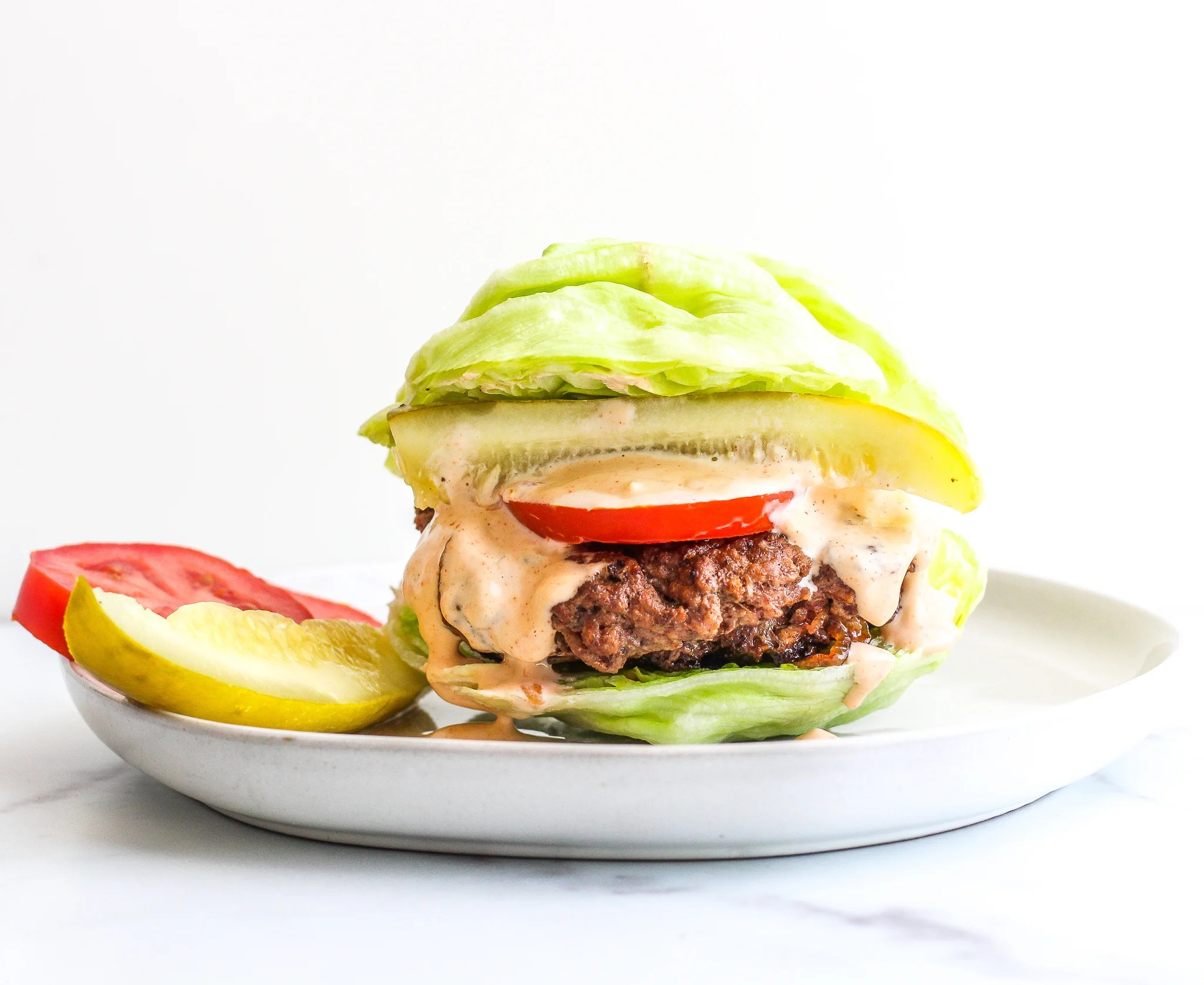 Caramelized Onion Stuffed Burgers on a lettuce bun topped with creamy spicy garlic aioli and a pickle and tomato