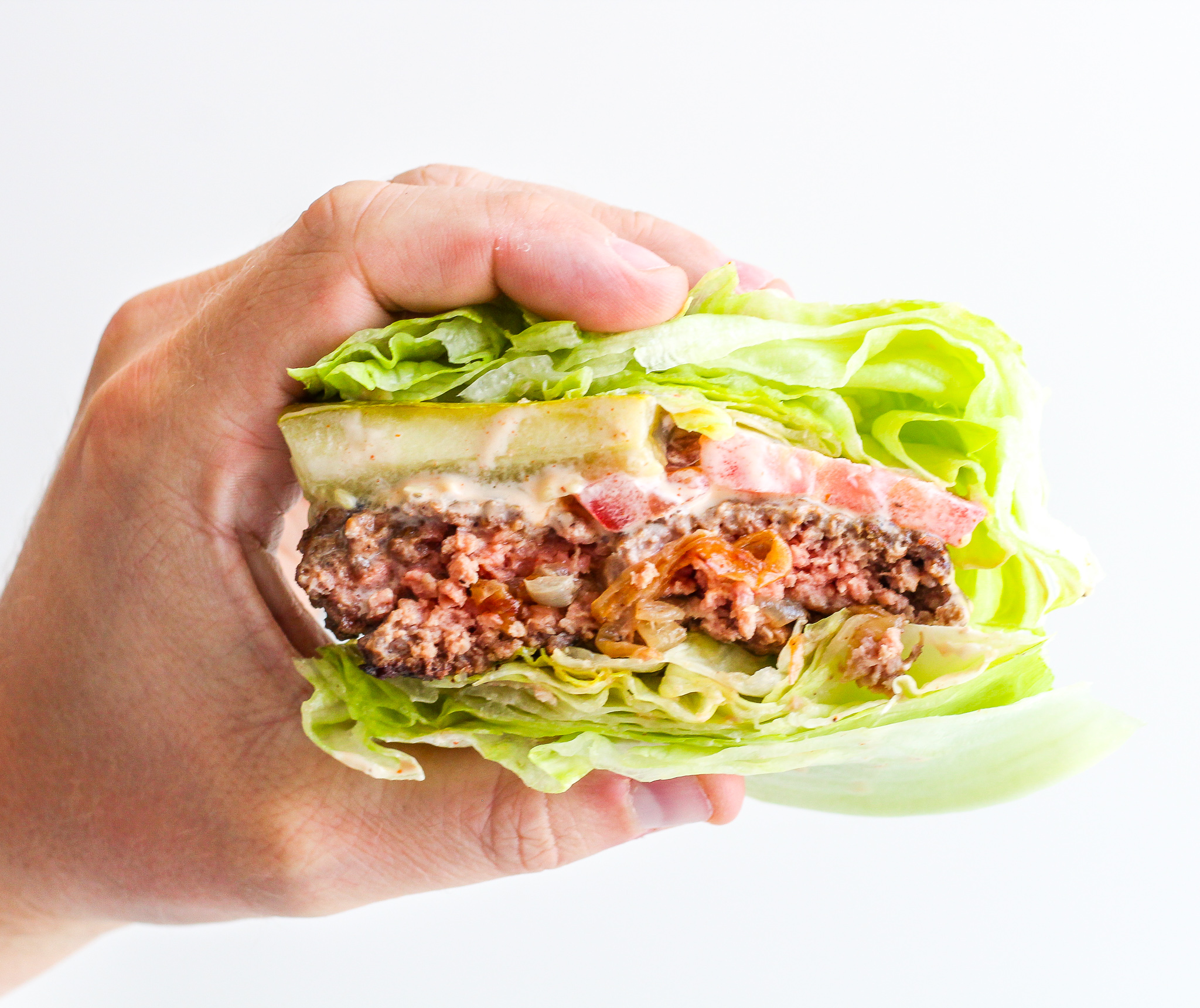 hand holding a Caramelized Onion Stuffed Burger