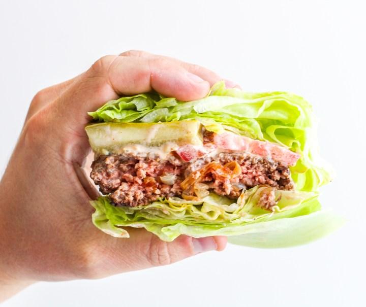 hand holding a Caramelized Onion Stuffed Burger