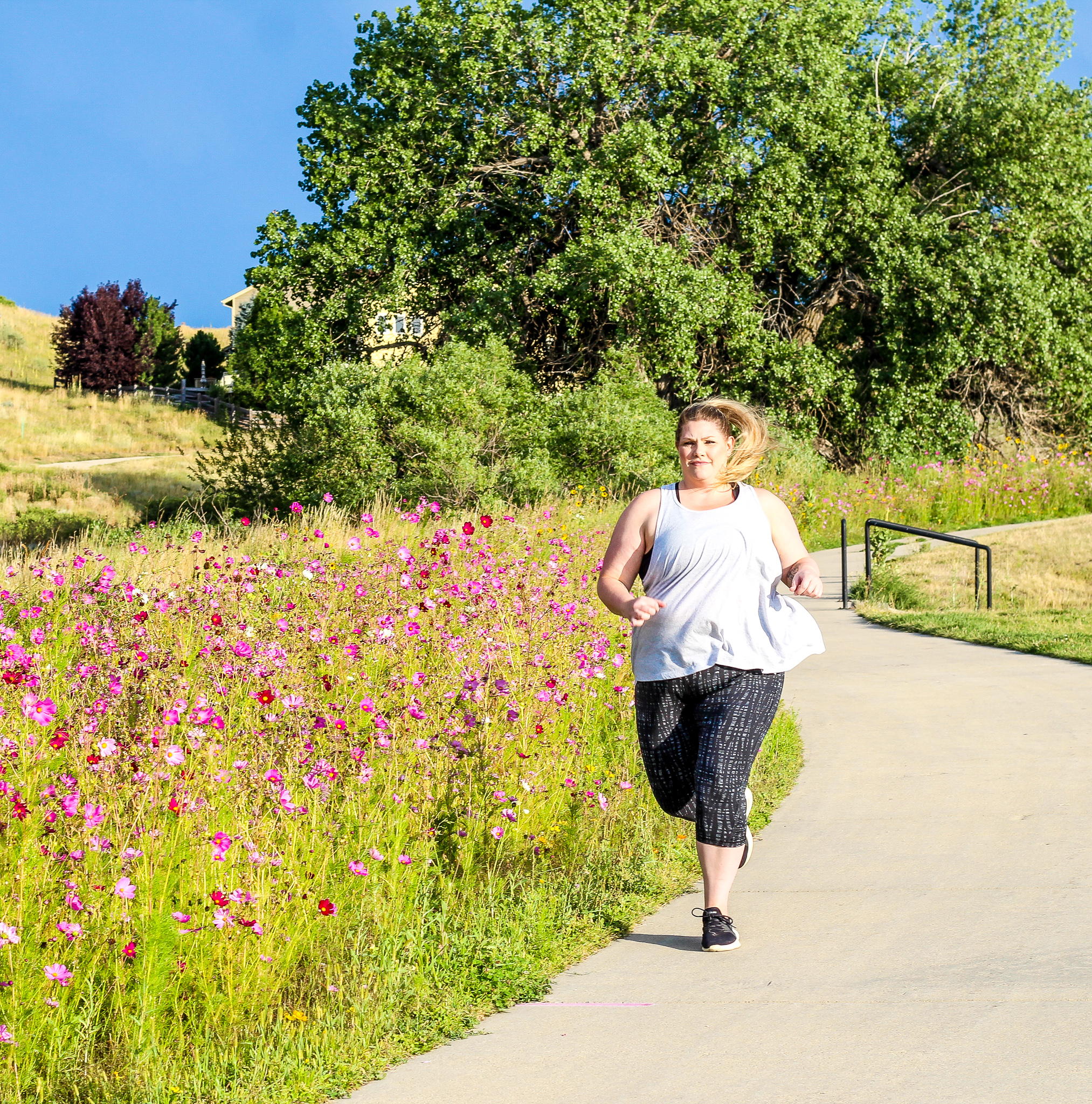 Plus size woman running outside by pink flowers and green trees