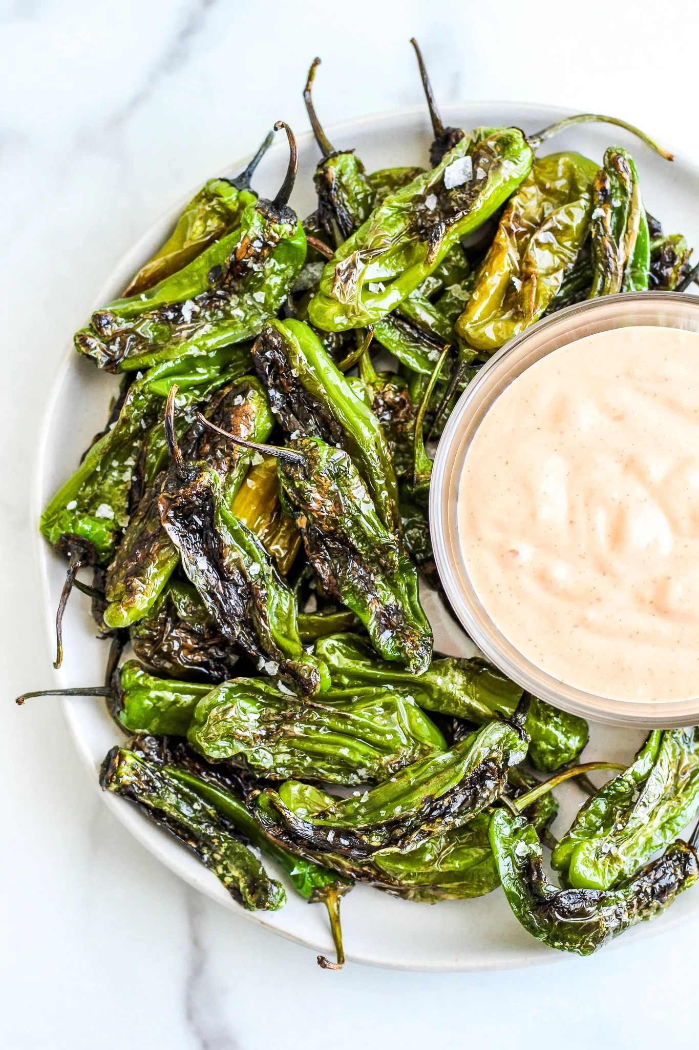Pan Roasted Shishito Peppers on a plate with a bowl of aioli