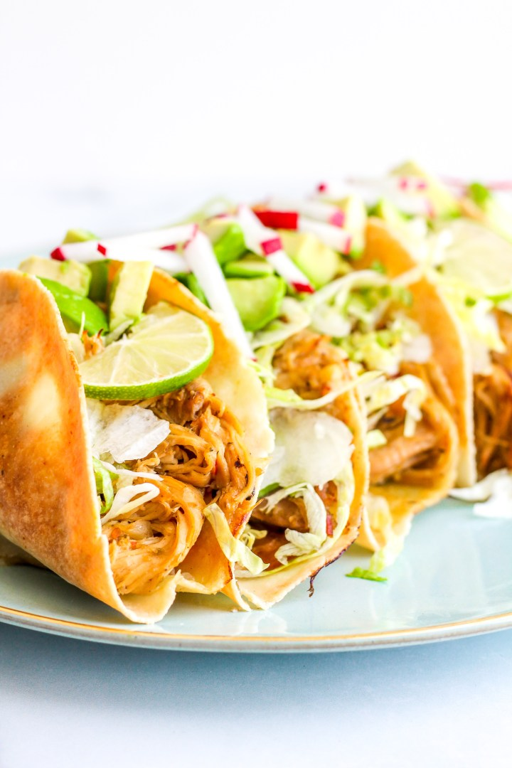 Side view of staked baked chicken tacos topped with lime slices, diced avocado and radish
