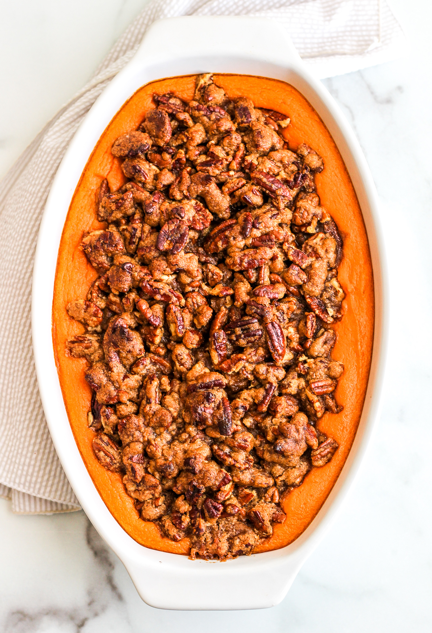 Sweet Potato Casserole topped with Pecan topping in a white serving dish