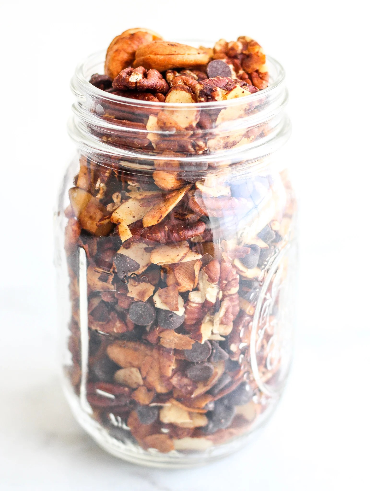 keto trail mix of almonds, cashews, pecans, coconut flakes and sugar free chocolate chips in a clear mason jar