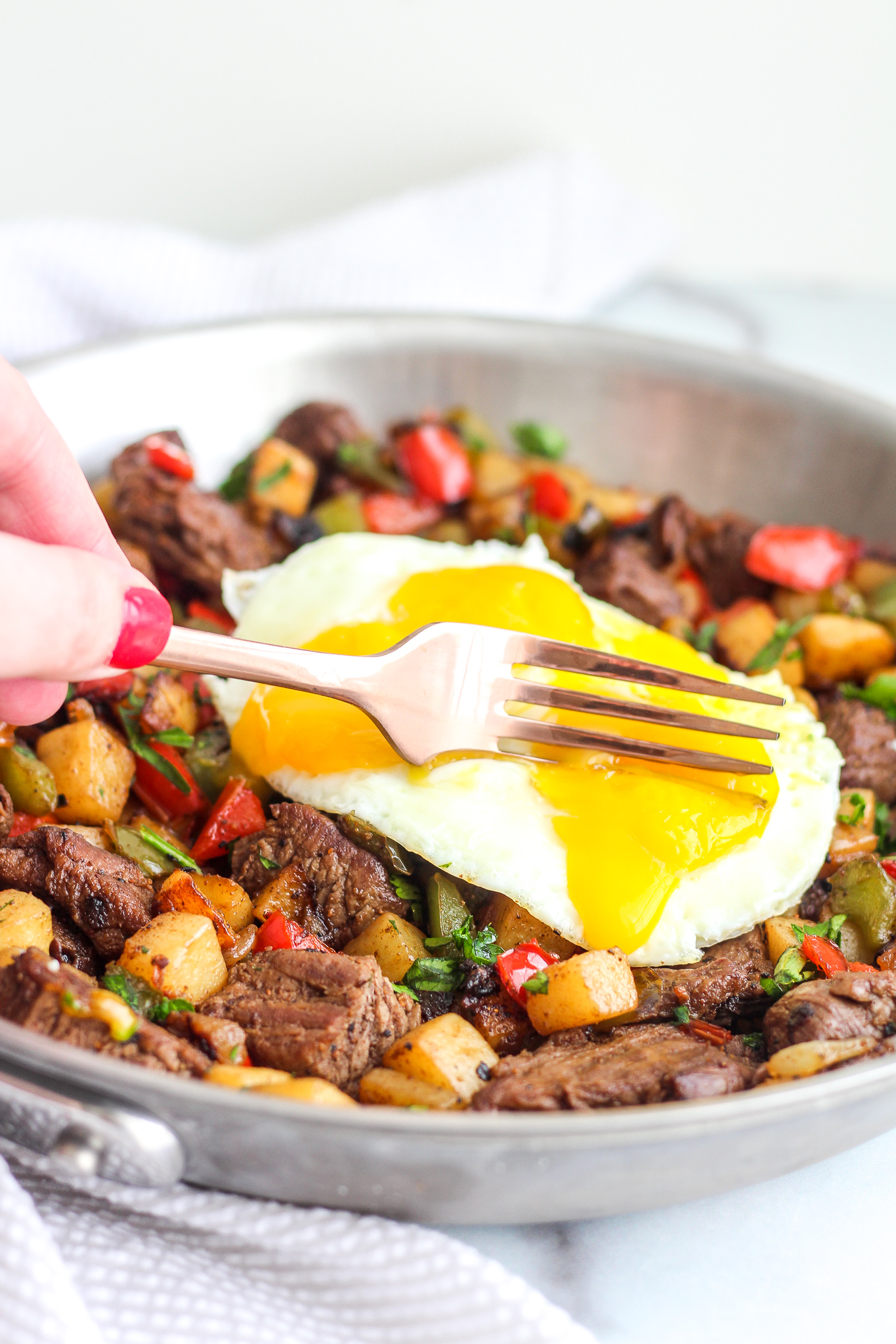 Fork cutting into a perfect runny egg yolk over Whole30 Steak Breakfast Hash