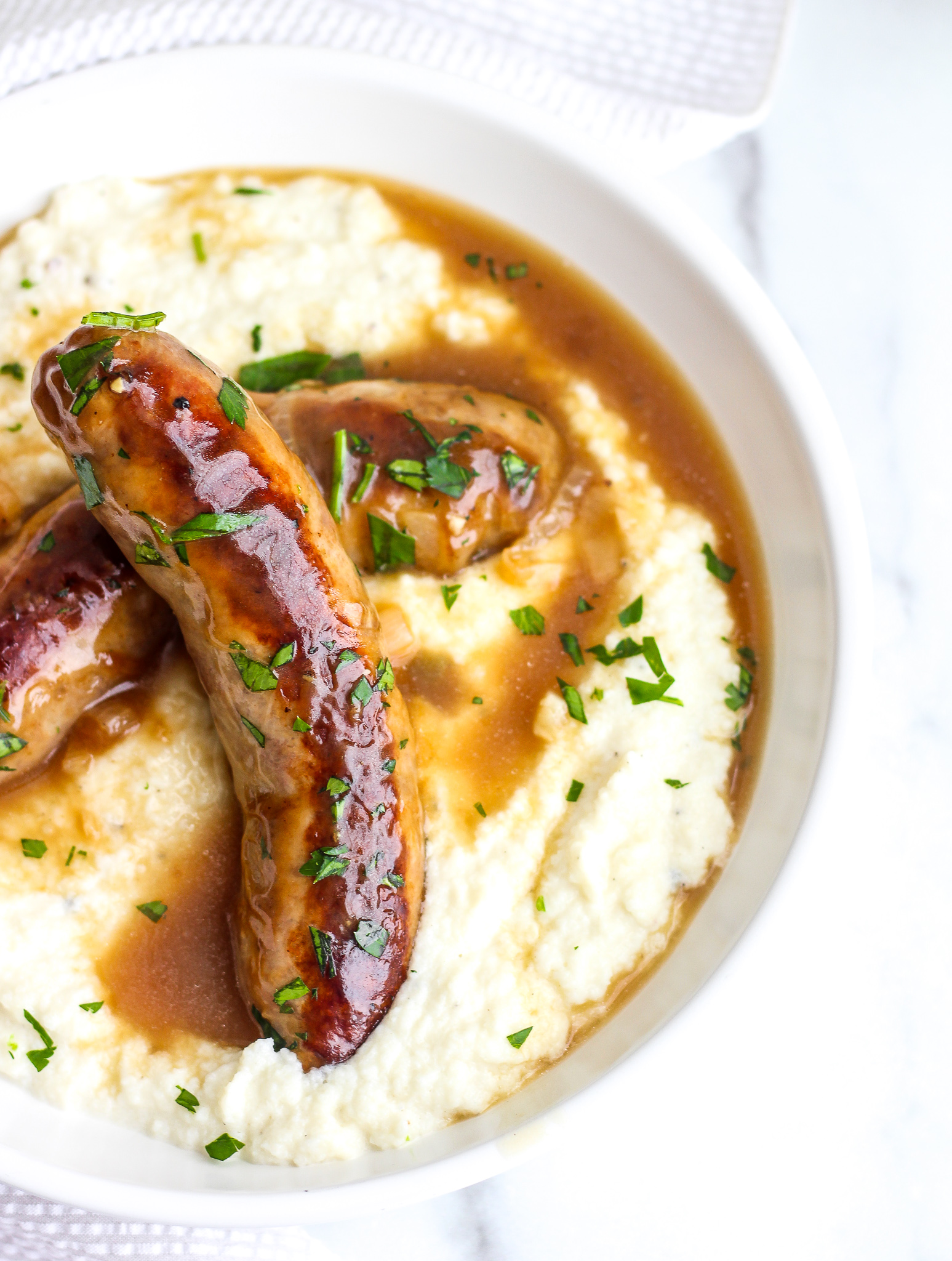 White bowl with creamy cauliflower mash topped with two browned sausages and onion gravy