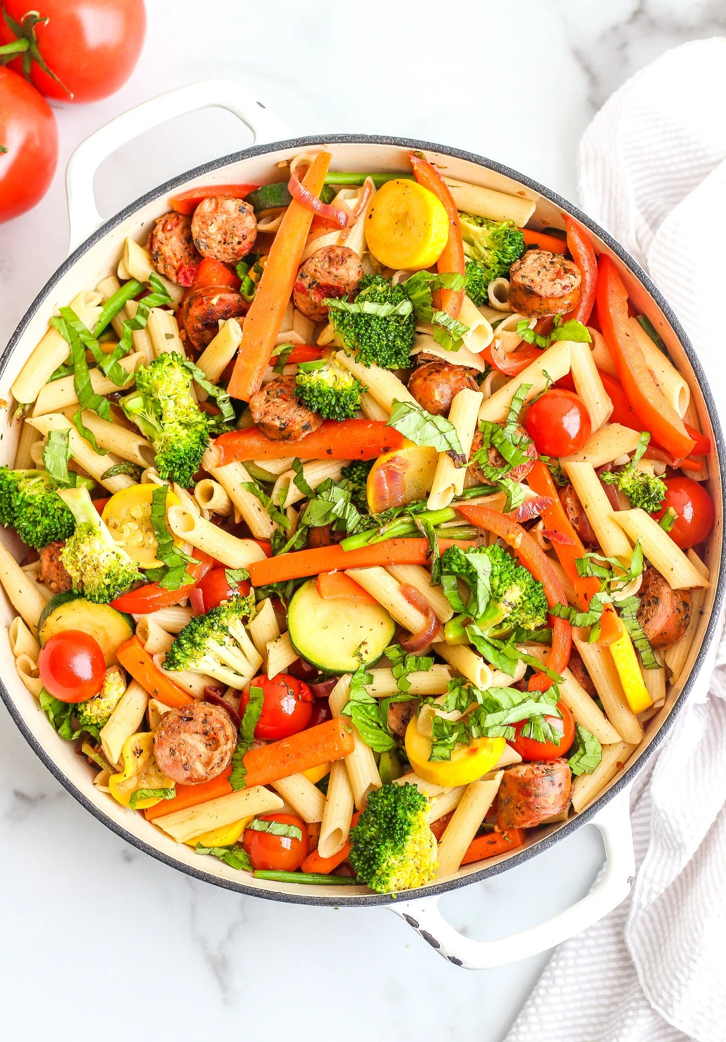 White pan filled with penne pasta, fresh veggies and chicken sausage