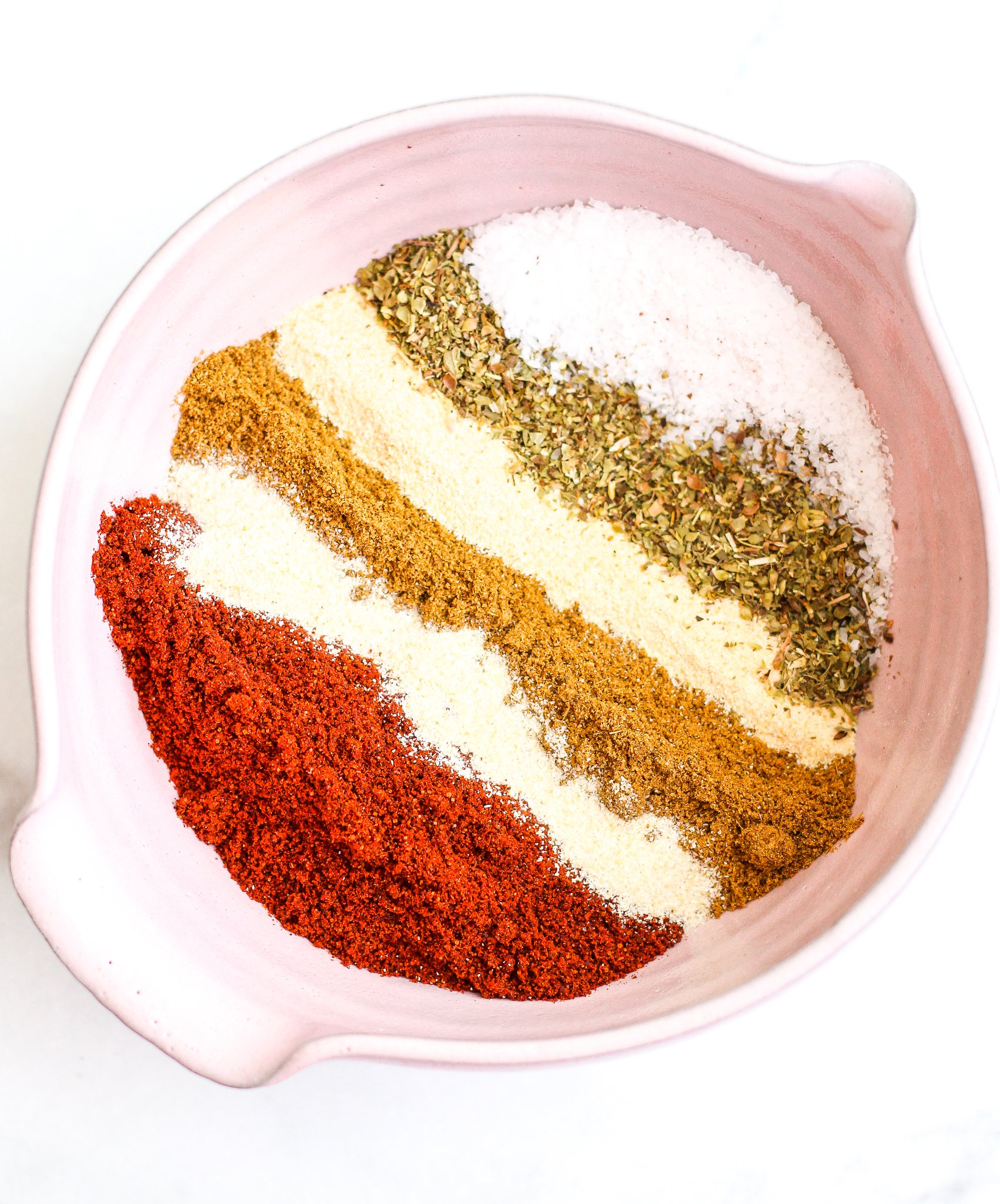Layers of spices in a pick ceramic bowl