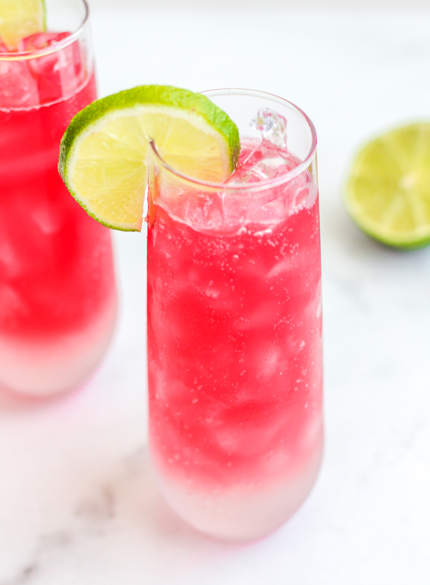 Cranberry ginger fizz mocktails in two tall clear glasses. The beverage is fizzy and pink with a lime wedge on top of the glass