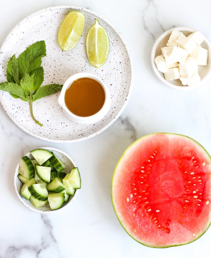 Flat lay of ingredients in the watermelon cucumber salad - watermelon, cucumber, fresh mint, lime wedges, feta cheese and honey lime dressing