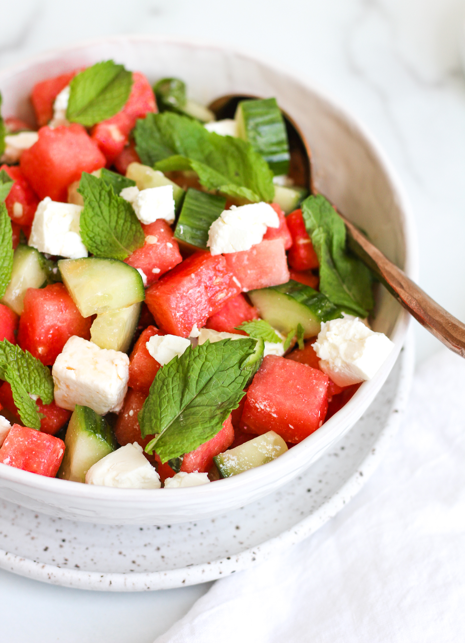 Watermelon cucumber salad in a white ceramic serving bowl topped with fresh mint and feta cheese