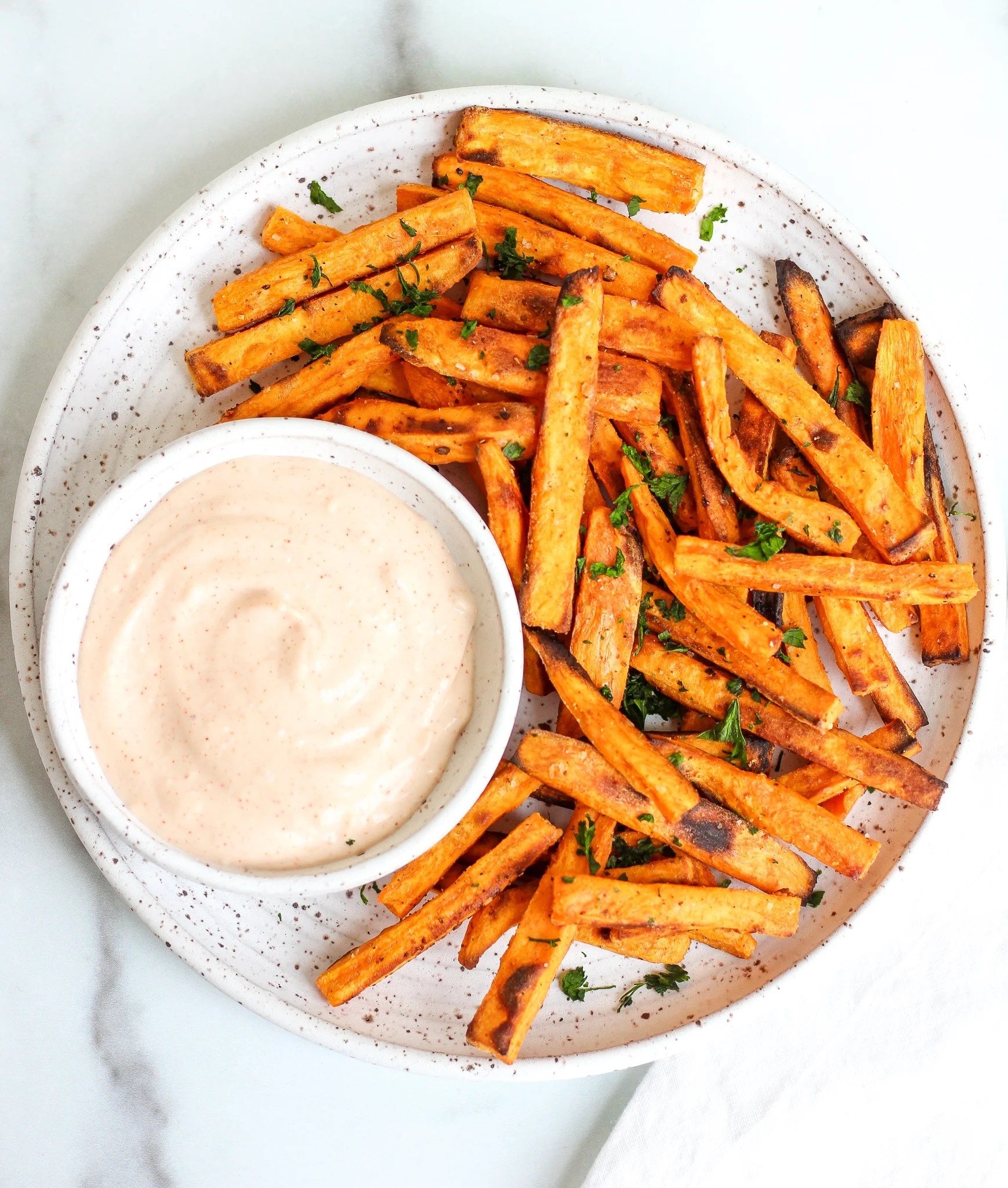 Oven baked sweet potato fries on a ceramic plate served alongside a spicy garlic aioli
