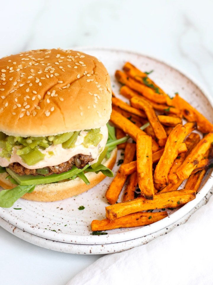 Green Chile burger on a bun next to oven baked sweet potato fries on a ceramic plate