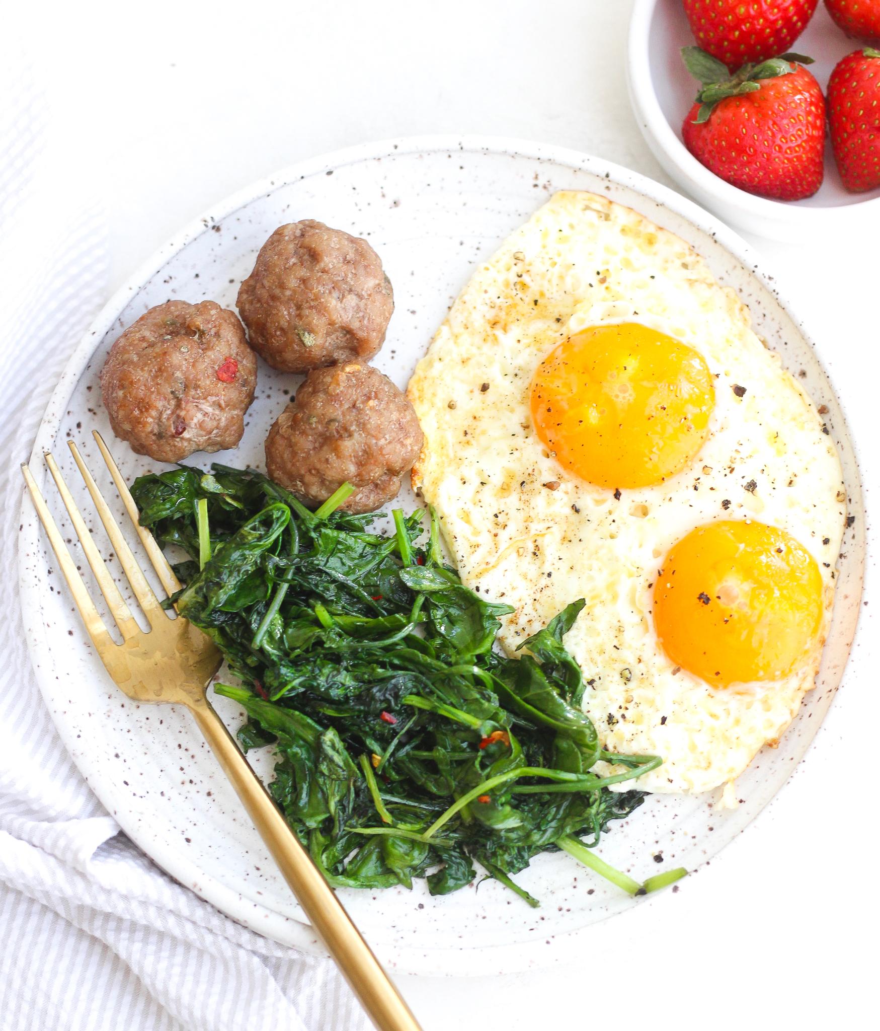breakfast meatballs on a ceramic plate served alongside sautéed kale and sunny side up eggs