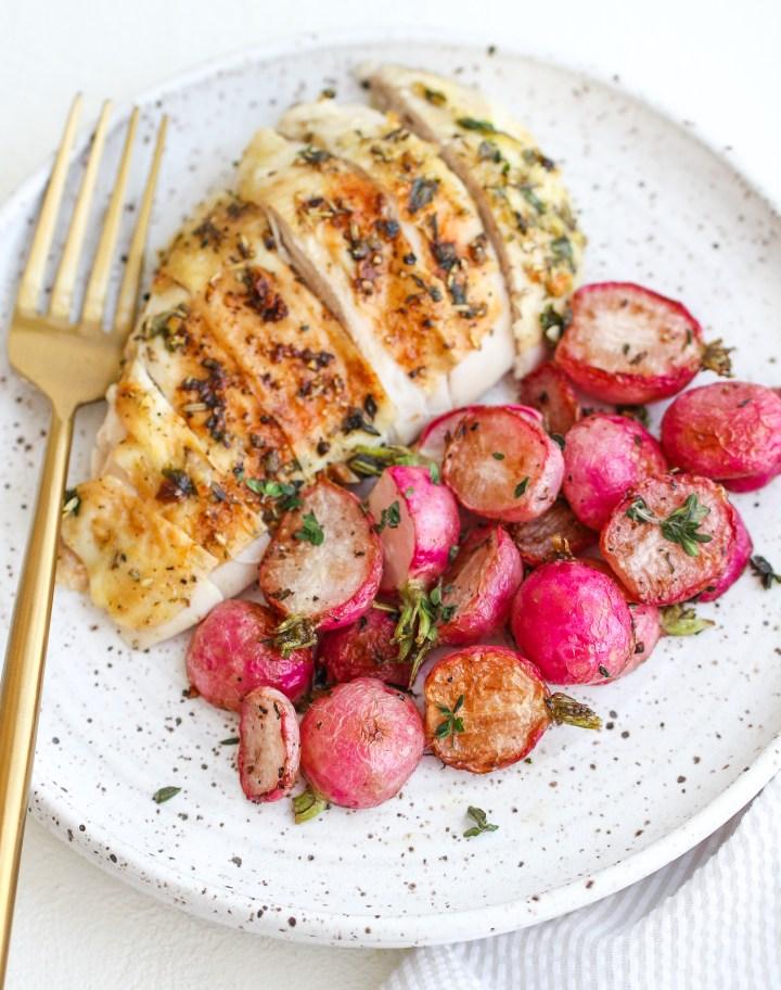 roasted radishes served alongside sliced herb roasted chicken breast