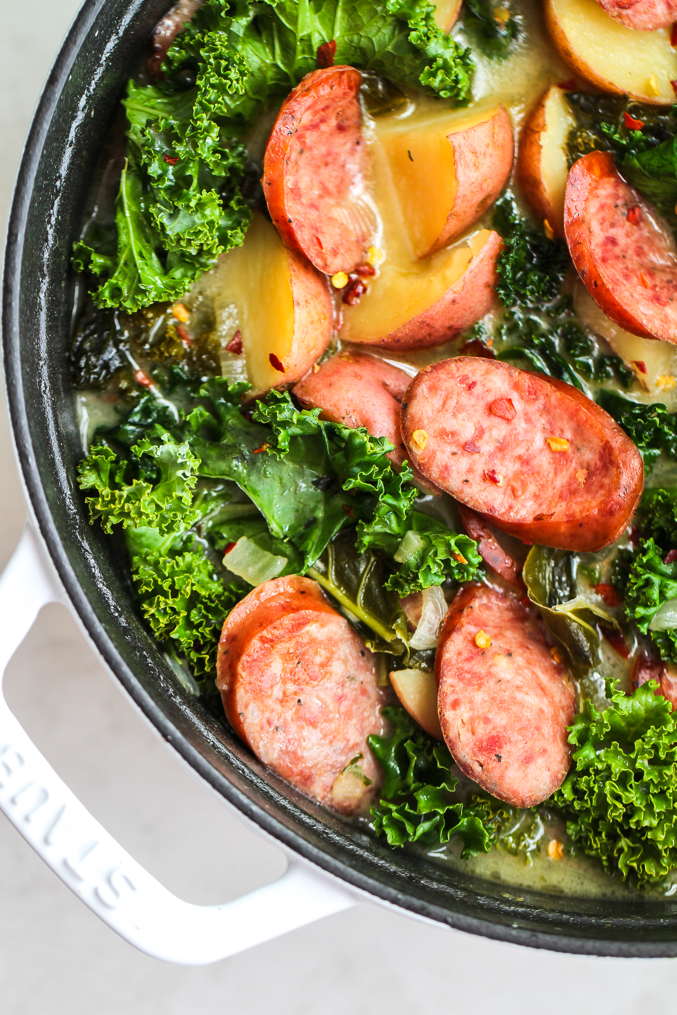 Sausage, kale & potato soup in a white soup pot, topped with pepper flakes