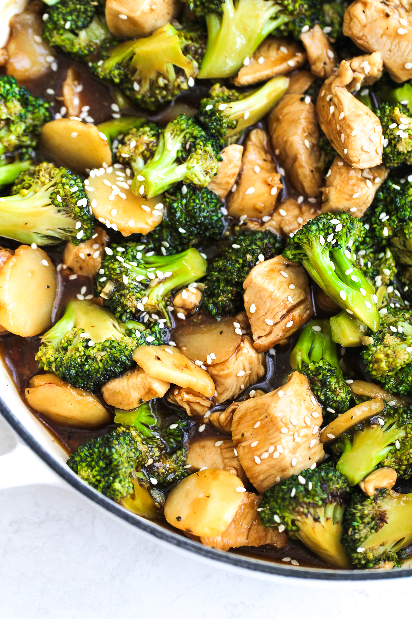 chicken broccoli stir-fry in a large white skillet topped with white sesame seeds