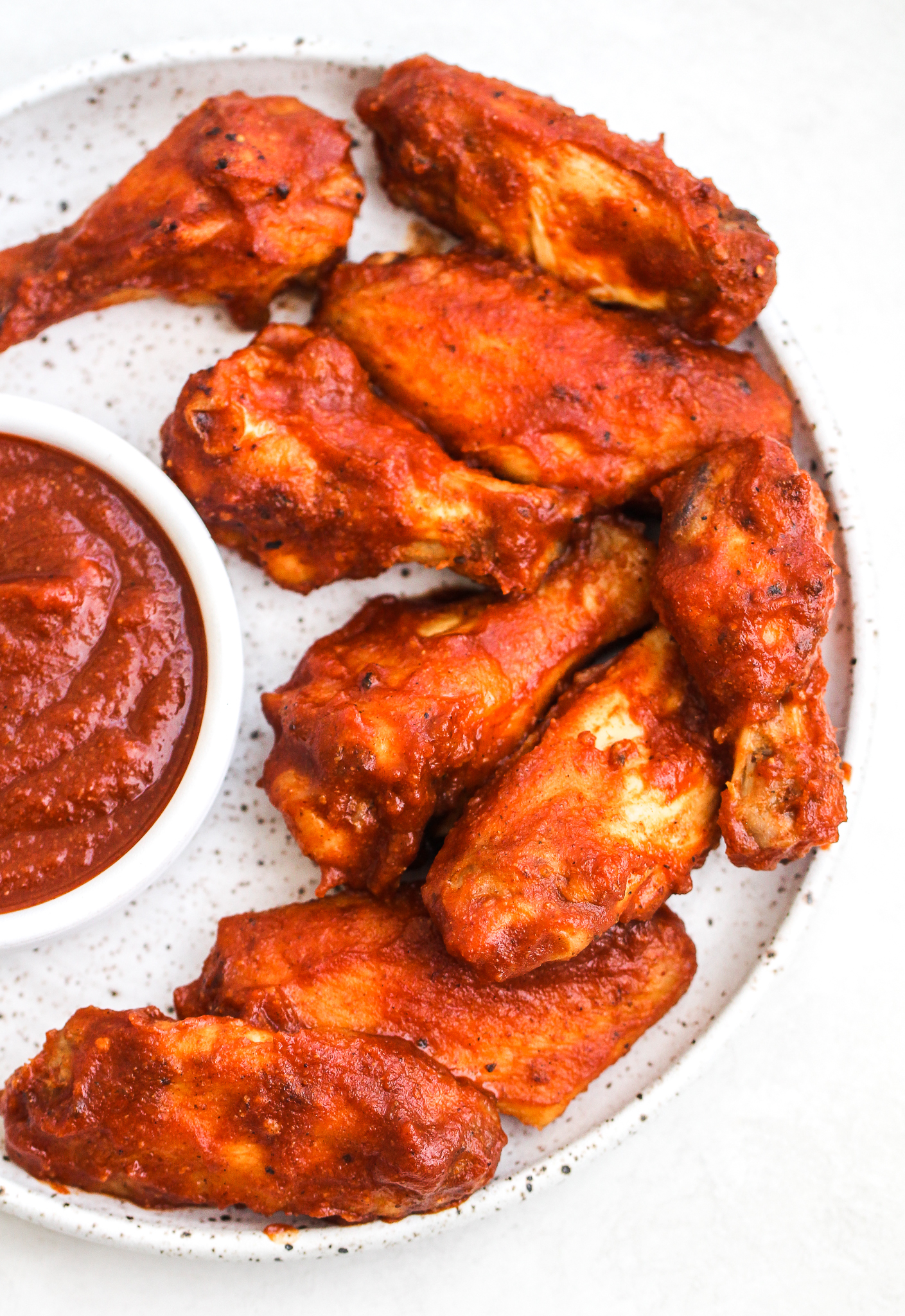 BBQ chicken wing sections on a speckled ceramic plate with a side dish of BBQ sauce
