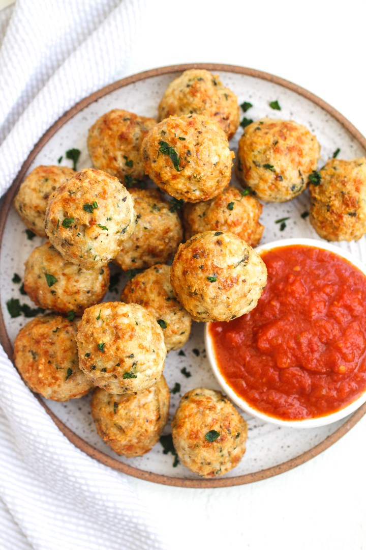 Crispy chicken parmesan meatballs on a ceramic plate topped with fresh parsley and served with a side of marinara sauce